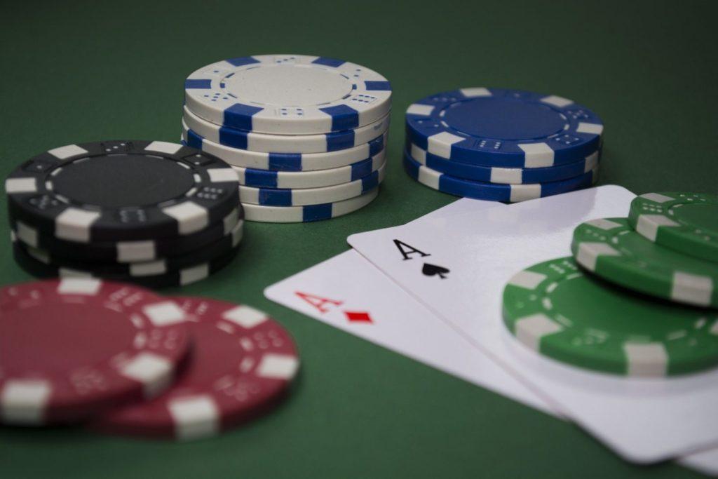 Zwei Asse liegen unter grünen Spielchips auf dem Tisch